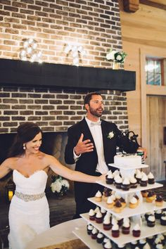 Katey and Tony play it up at the wedding cupcake table - nice style, y'all! | Photo by www.monikagauthier.com #weddingcupcakes