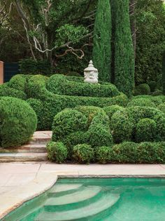 Clouds of trimmed boxwood swirl around an antique Italian stone urn, and paths meander among the cypress.