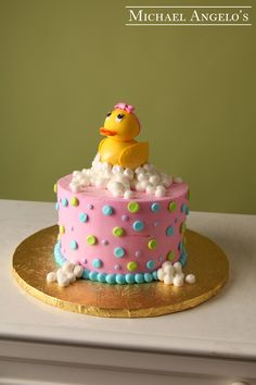 Girl Rubber Duckie #38Baby This cake is iced in buttercream with colorful polka dots all over. The topper is a gum paste rubber duckie with a cute little pink bow for any baby girl.