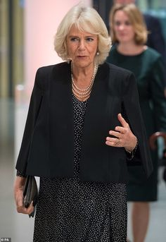 ein a black and white patterned dress, which she wore under a short black cape