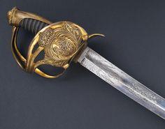 """R-E36B.- Sable para oficial de la Guardia Real. España, hacia 1825. Guarnición en latón sobredorado de. En el frontal un gran escudo con las Armas de España. Monterilla larga, con cordón labrado y virola en la base. Galluelo firmado """"L.Boreti"""". Puño de madera gallonado forrado con piel de lija. Excelente hoja curva, firmada """"S & K"""" (Schnitzler & Kirschbaum), grabada y pavonada azul en su primera mitad. Long. Total: 102 cms  Long. Hoja: 87,5 cms  Anchura base hoja: 33 mm Powder Horn, Ninja Weapons, Sword Fight, Swords And Daggers, Conquistador, Cold Steel, Bronze Age, Knife Making, Rare Antique"""