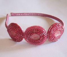 Tiara forrada com fita de cetim e 3 enfeites bordados de vitrilhos rosa magenta.