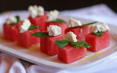 summer snack  watermelon cubes garnished with mint and feta with a drizzle of olive oil...