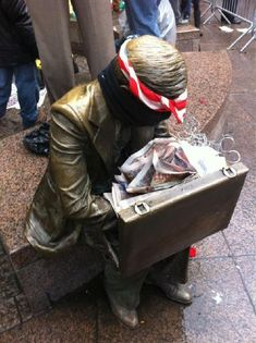 "Daytonian in Manhattan: John Seward Johnson II's ""Double Check"" -- Zuccotti Park  The park took on a new personality about five years later when it became base for the Occupy Wall Street protestors.  In their fervor to denounce anything remotely capitalist, they stuffed trash in the sculpture's briefcase, tied a mask around his face and a bandana on his head.   The statue that had become a memorial to the deaths of 3,000 innocent lives became a symbol of decadence to the protestors."