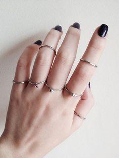 vários anéis prateados finos e simples nos dedos.