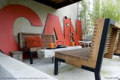 A large sign spelling CAN dominates the rear wall of this outdoor room which is furnished with two large benches and a table fashioned out of an old beam