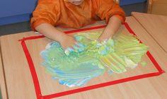 Scheerschuim mengen met verf. Ideaal om vormen in te tekenen en kleuren te leren mengen. Als de kleuters er vormen in hebben getekend, kan je er nog een afdruk maken op een blad. Zo hebben ze een blijvend aandenken.