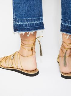 Opulence Wrap Sandal   Elastic and strappy, these metallic sandals feature an adjustable ankle strap with charm and tassel ends.    Size Guide:   Small: US shoe size 5-6   Medium: US shoe size 7   Large: US shoe size 8-9   Extra Large: US shoe size 10