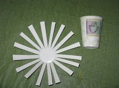 Cut slits down the side of a paper cup to make the base of a basket. Then weave raffia or another materials over and under the strips to make a basket.