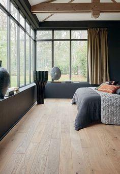 Chambre contemporaine baignée de lumière naturelle avec vue panoramique sur le jardin. Au sol, parquet clair en chêne blanchi, Zenitude Linen Otello, collections PANAGET.