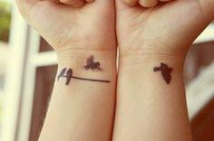 Pequeños tatuajes de varios pájaros en la muñeca.