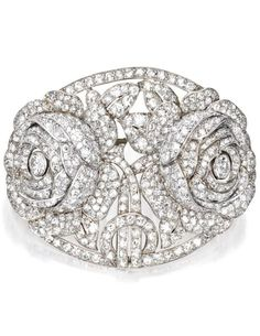 Lacloche - A Belle Epoque Platinum and Diamond Brooch, Paris, Circa 1915. The oval-shaped plaque depicting two roses, set with old European, single and rose-cut diamonds weighing approximately 7.50 carats, signed Lacloche Paris, numbered, with French assay and workshop marks. #Lacloche #BelleÉpoque #brooch