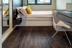 Dark vinyl floors with a natural wood look from the Amtico Vinyl Spacia Collection in ember oak shade. Perfect for high traffic areas or anywhere that spills and drips may occur.