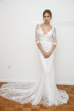 Fit-and-flare lace wedding dress with textured overlay and sheer long sleeves with embroidered detail by @vkkny | Bridal Market Fall 2016