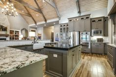 Green and gray kitchen // Black and white granite countertops, white apron farmhouse sink, island, bar seating, stainless, tons of cabinetry