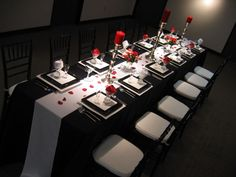 Elegant black and white wedding table setting with red accents