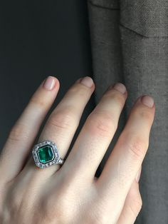 Art Deco Cartier ring centering upon an emerald-cut emerald weighing approximately 1.60 carats with AGL certificate stating the emerald is Colombian natural. Surrounded by 16 baguette and 4 single-cut diamonds. Set in platinum. Signed and numbered. Circa 1925