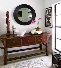 """A clever juxtaposition of old and new gives the master bathroom distinctive personality. The homeowners opted to use a well-weathered Chinese butcher table as a vanity, maintaining the authenticity of the piece with an above-the-counter vessel sink. A pebble tile """"rug"""" in the center of the space provides another layer of texture and delivers a good massage to bare feet./"""