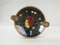 This is a vintage plastic ashtray containing a dried flowers bouquet. Yellow red and white flowers are enclosed in a curved glass front. It has a gold brass frame with two brass cigarette holder. Dried Flower Bouquet, Dried Flowers, Red And White Flowers, Cigarette Holder, Curved Glass, Brass, Plastic, Yellow, Unique Jewelry