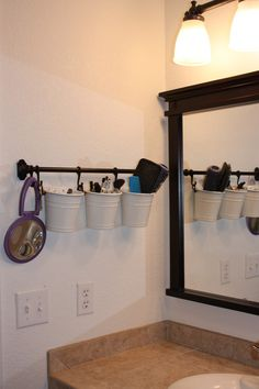 clear up counter space in bathroom... buckets on rod