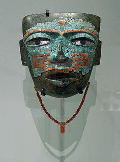 """Teotihuacan y México Occidental  Guerrero, Malinaltepec Período clásico medio, 300 - 550 d.C. Piedra con incrustaciones de turquesa, amazonita, obsidiana y conchas; collar de 55 perlas y un pendiente  Esta máscara fue hallada en las costa del Pacífico de México Occidental adonde debe haber llegado a través del comercio o de las guerras. Originalmente estaba completamente cubierta con piedra turquesa. En la frente tiene el símbolo correspondiente a """"agua que fluye""""."""