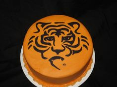 "Tiger themed cake. To do this print a stencil and cut out the black lines (I use an exacto knife blade for clean cuts).  Roll out black fondant onto a greased sheet of wax paper 1/16"".  lightly dust the fondant with cornstarch/powder sugar and place your stencil onto the fondant (flipped over!) Using the blade or sharp knife cut out the lines. Lift stencil and remove excess fondant. Lightly wet with sugar water and flip onto the cake surface. Lightly rub with finger and roll back wax paper."
