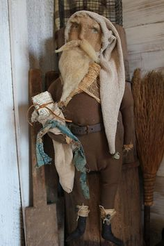 cinnamon creek dry goods | 2015 | Santa hanging - 24'' long. Dark tan canvas suit, old leather belt, oatmeal colored sock cap and a simple gift in his sack. His face is made from an old cotton sock that is handpainted in a simple naive way. Sheeps wool beard. 95.00 plus shipping SOLD