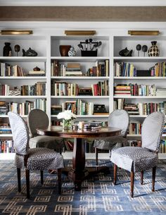 """Chicago designer Tom Stringer Chicago home library  In the library of his home, Louis XVI–style chairs surround an antique English tilt-top table that, Stringer writes, is """"ideal for backgammon and cards."""" The designer covered the walls around the bookshelves with men's suiting flannel."""
