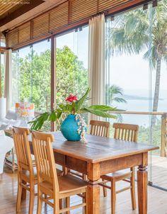 Sala de jantar conta com mesa de madeira de demolição e vaso com arranjo de plantas tropicais.