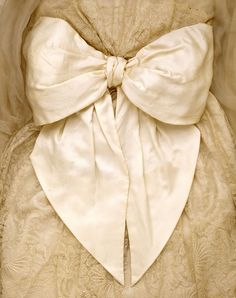 c.1912-14. The gown has a wide, high-waisted sash which ties behind in an enormous butterfly bow. The bow is entirely decorative. Although it looks soft and supple, it is actually lined with stiff organza and is wired at the edges. The bodice and sleeves are cut in one piece. A silk machine-lace panel attached at the bust forms the overtunic which is gathered at the waist and falls in soft folds to the hips.