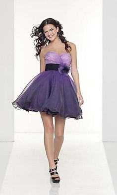 SEMI FORMAL SHORT PURPLE DRESS BY MORI LEE 9041  Purple is the color of royalty and you'll feel like a princess in this ravishing short purple dress by Mori Lee. Perfect for formal dances, semi formal parties, and holiday celebrations this short dress features a strapless bodice with sweetheart neckline, banded waist with flower accent, and a flared layered skirt in sensational organza fabric.