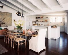 Modern pendant lamps hang over a wooden dining table.