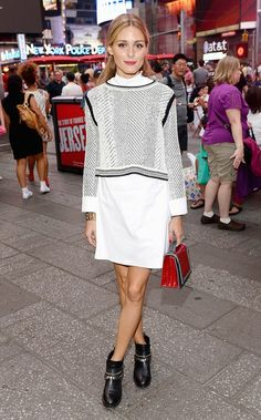 Olivia Palermo wears a white shirtdress, sweater, top-handle bag, and metal-embellished ankle boots