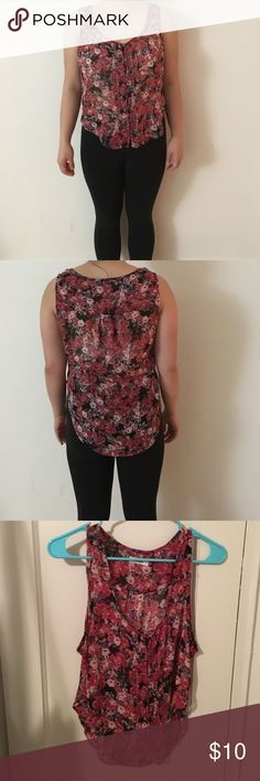 This is a floral sleeveless top size small This is a lightly worn floral sleeveless top. The colors are red, white with hints of black and green. It has button detailing down the front. It has flowing lines. Garage Tops Blouses