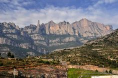 Montserrat is a multi-peaked mountain located near the city of Barcelona, in Catalonia, Spain. It is part of the Catalan Pre-Coastal Range. The main peaks are Sant Jeroni (1,236 m), Montgrós (1,120 m) and Miranda de les Agulles (903 m).  It is well known as the site of the Benedictine abbey, Santa Maria de Montserrat, which hosts the Virgin of Montserrat sanctuary and which is identified by some with the location of the Holy Grail in Arthurian myth.