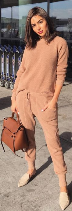 Who made Olivia Culpo's brown handbag, tan pants, sweater, and handbag?