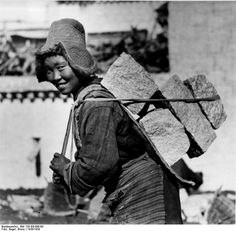 Tibet, Lhasa. Young woman carryng stones. From Nazi's Tibetexpedition.  Photographer 	Beger, Bruno. 1938
