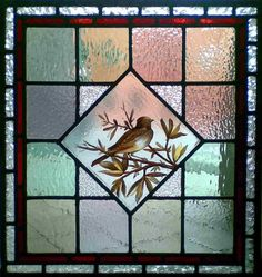 Antique Victorian hand-painted bird in stained glass window.