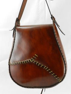 This bag is made of 7/8 oz. re-tanned yellow latigo and features a flap of the natural edge of the hide. This portion of the hide is the leg and its unique characteristics occur naturally in the tanning process. The front panel features an antler tip for the lace tie-down closure and the back features a crude looking stitched repair and patch for aesthetics and interest. The cut-out in the front panel provides easy access to this spacious bag. This bag is uniquely a one-of-a-kind bag and...