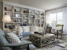 I really like the soft, neutral pallete used in this living room. Grey is the new neutral and the subtle touches here mixed with white and that great rug make this a very pretty room that looks casual and formal at the same time. Love the full wall of book shelves.    South Shore Decorating Blog: Neutral Rooms