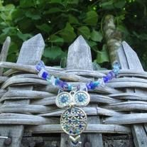This necklaces features a moveable owl pendant (the body swings separately from the head). With large colorful eyes and a decorated body, the blues teals and purples in this owl give it an enchanted feeling. It is perfectly matched with glass stone chips in blue, purple, clear and light teal. It ...