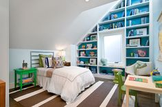 Kid's room with tall ceiling boasts a sloped ceiling fitted with built-in bookcases with backs of shelves painted blue surrounding a window seat bench.