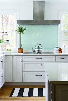 teal backsplash, cabinet handles, clean and fresh kitchen.