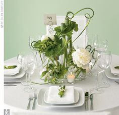 A collection of vases is given a cohesive feel with lush greenery like poppy pods, curly allium, and white peonies.