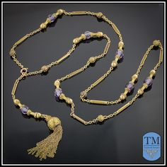 10K Gold Sautoir Necklace with Purple Gloass Beads --- Sautoirs, long opera style necklaces with tassels, were popular fashion accessories worn with flapper dresses during the Roaring 1920s. This 10k gold sautoir necklace accented with faceted purple glass beads features outstanding craftsmanship. Each of the rectangular links contains a delicate coiled gold wire decoration and each gold bead is decorated with delicate etruscan-style gold wirework.