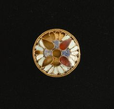 AN ACHAEMENID INLAID GOLD BUTTON c.a 6th-4th century b.c. a quatrefoil lotus motif, the petals of inlaid lapis, carnelian and turquoise, found: christies.com