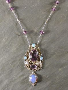 Dorrie Nossiter (attrib). An Arts and Crafts pendant necklace, the central facetted amethyst stone surrounded by a network of vines and opal cabochons with further cut amethyst stone and cabochon opal pendant drop, the twisted link chain amethyst stone spacers. Also attributed to Sibyl Dunlop as well as Dorrie by the auctioneers, but is clearly by Dorrie. Sold by Lyon and Turnbull. Discussed on http://www.dorrienossiter.co.uk/designs/misattribution/altered-pieces.html