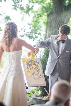 bride and groom pouring paint overs a canvas during their ceremony