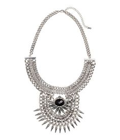 Short metal chain necklace with a large, decorated pendant of faceted plastic beads. Adjustable length, 17 3/4 - 20 3/4 in.