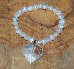 Bracelet perles blanc avec coeur nacre. Elastique pour s'adapter à tous les poignets.